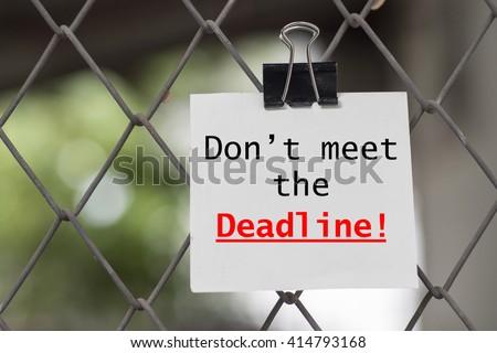 Note with the phrase don't miss the deadline on steel wire mesh fence background - stock photo