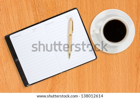 Notebook and coffee cup on the wooden table