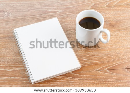 notebook and coffee on wooden background
