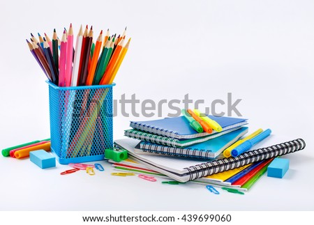 Notebook and copybook stack with metal holder pencils, pens, paper clips, sharpener and eraser on a white background. Back to school concept
