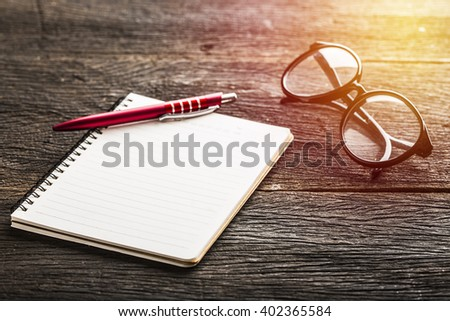 Notebook and glasses and red pen on table. Vintage filter - stock photo