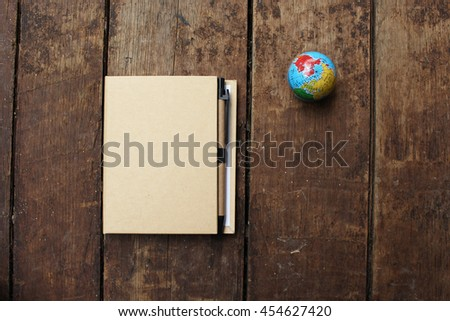 Notebook and globe - travel concept - stock photo