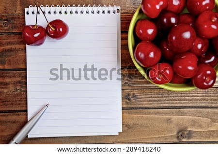 Notebook and green bowl with cherries on table