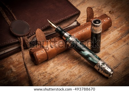 Notebook and luxury vintage pen on wood table