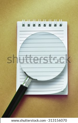 Notebook and magnifier glass on a brown paper background. Conceptual image of fundamental, planning , implementation, solution and business strategy.