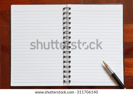 Notebook and pen. Blank white page. Wooden floor in the background.
