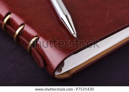 Notebook and pen in composition in black - stock photo