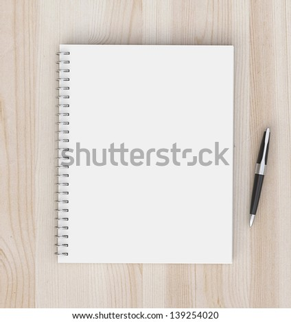 notebook and pen on a wooden background - stock photo