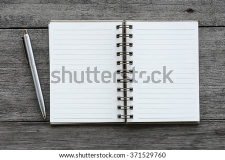 Notebook and pen on the wooden floor. - stock photo