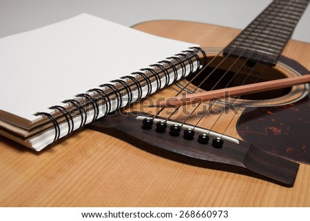 Notebook and pencil on guitar