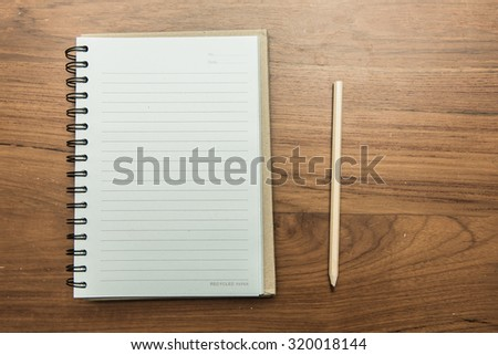 Notebook and pencil on table. - stock photo
