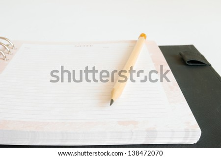 Notebook and pencil on white background.