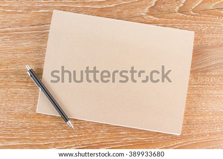 notebook and pencil on wooden background