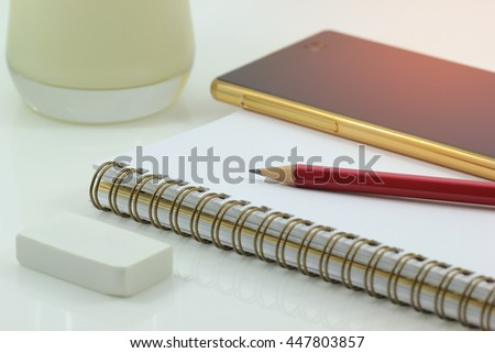 Notebook and pencil with smart mobile phone on white background