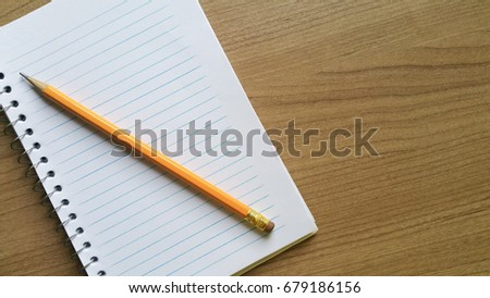 Notebook and school pencil on wooden table