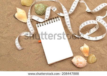 Notebook and tape measure - stock photo