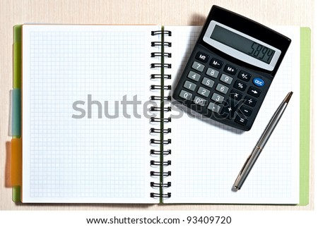 Notebook, ballpen and calculator on wooden desk - stock photo