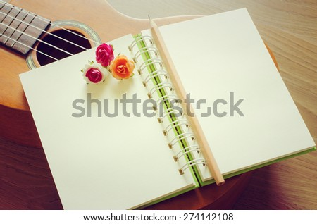Notebook blank and pencil on Ukulele music instument with vintage background - stock photo