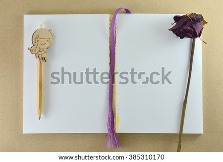 Notebook.Blank notebook with dry flower and pencil. - stock photo
