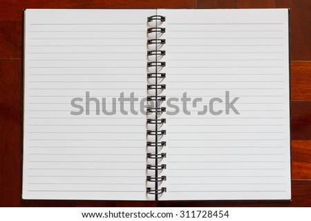 Notebook blank white page. Wooden floor in the background.