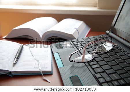 Notebook,book, laptop, pen and glasses.