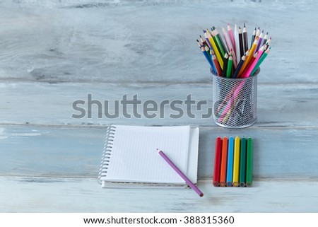 Notebook bright color pencils stationery on old wooden table vintage background - stock photo