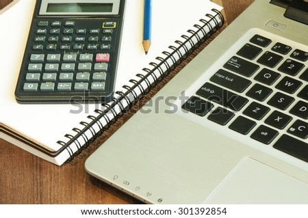 Notebook Calculator pecil and laptop on wood - stock photo