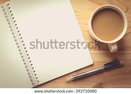 notebook checked with a  pencil   and a cup of coffee , vintage tone - stock photo