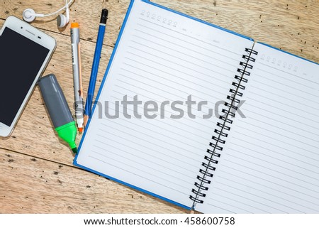 notebook, coffee, smartphone and pencil on wood desk.