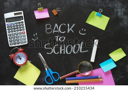 Notebook , colored pencils, back to school concept surface with copy space over blackboard background - stock photo