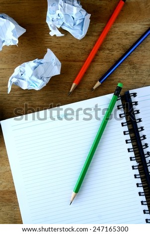 Notebook, crumpled papers and colorful pencils Photo of a Notebook, crumpled papers and colorful pencils on a wooden table - stock photo