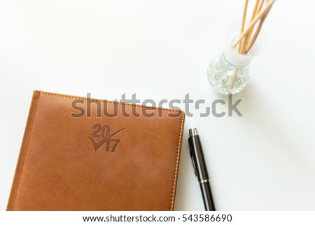 Notebook for new year 2017, fountain pen and ink pot on white ground