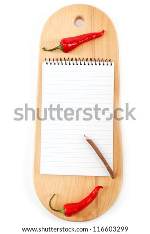 Notebook for recipes and spices on wooden board.