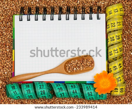 Notebook for the recipe of a buckwheat diet with tape measure closeup - stock photo