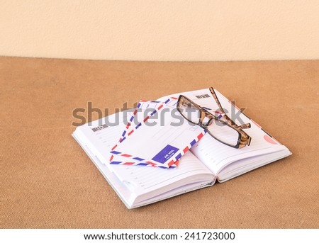 Notebook, glasses and envelope on wood background - stock photo