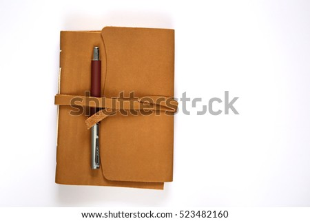 notebook  in brown leather cover, brown pen  isolated on white background