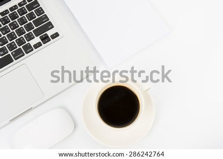 Notebook laptop and coffee cup on white table