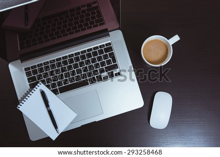 Notebook laptop and coffee cup on wood table - stock photo