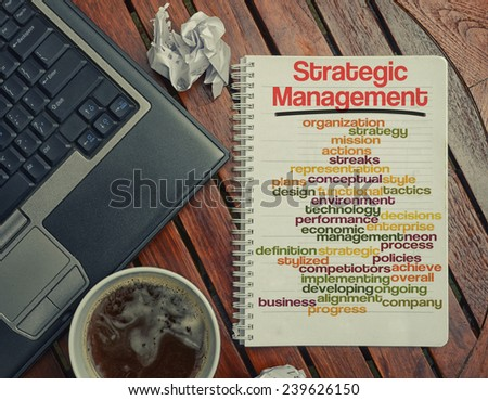 notebook lying on the table with the written words associated with the Strategic Management , on the table are also laptop and cup of coffee, notes made in the form of the cloud of words - stock photo