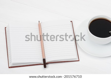 Notebook Mock Up And Cup Of Coffee On White Painted Wooden Desk. - stock photo