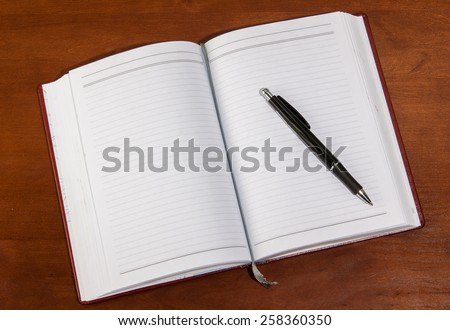 notebook on a wooden table. open diary and pen to record - stock photo