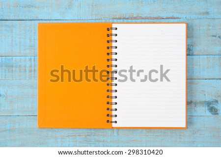 Notebook on blue wood table  for text and background - stock photo
