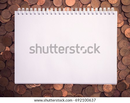 notebook on coins background with space for text