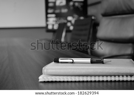 notebook on meeting table in conference room - stock photo