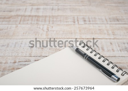 Notebook on wood table for background