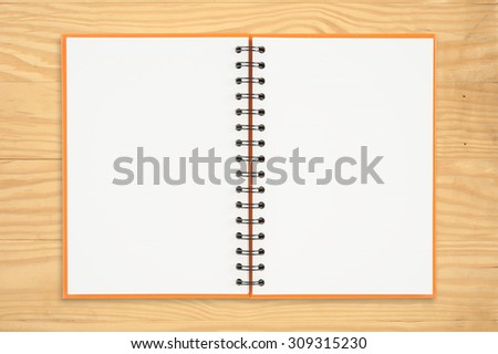 Notebook on wood table for text and background.copy space
