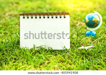 notebook on yard with airplane and globe  in garden on morning sunlight. vintage color tone. - stock photo