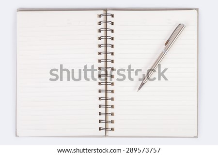 notebook open blank page with line and date text in the corner on white background, that has black spiral ring binder, and a silver pen put on the right page