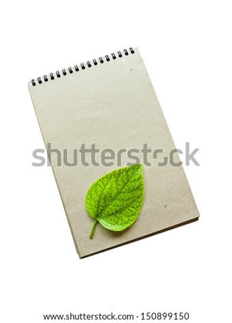 Notebook paper and green leaves on a white background. - stock photo