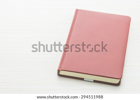 Notebook paper on wooden background